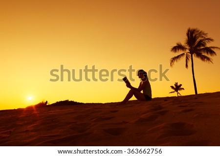 Woman relaxing and reading a book on the beach. - stock photo