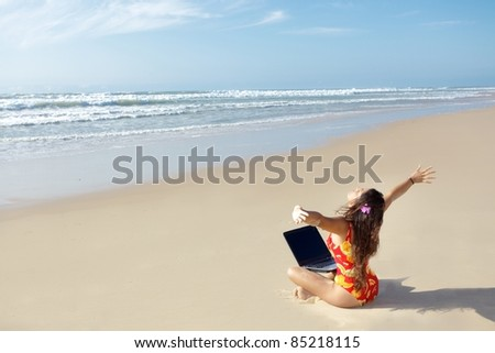 woman relaxing and using laptop on wild beach - stock photo