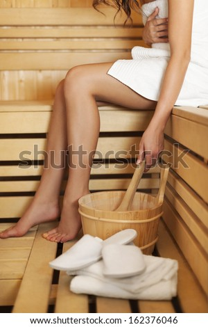 Woman relaxing and using sauna accessories - stock photo