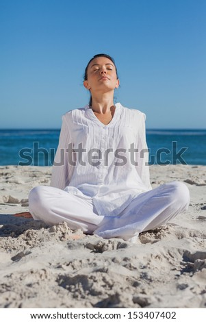 Woman relaxing at beach against ocean on a sunny day - stock photo