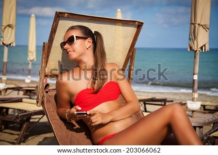 Woman relaxing at beach enjoying summer vacation. Beautiful girl on a deckchair with mobile phone in the beach of French Riviera.  - stock photo