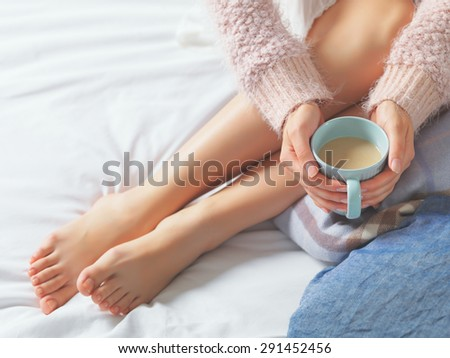 Woman relaxing at cozy home atmosphere on the bed. Young woman with beautiful skin and nails with cup of cocoa or coffee in her hands enjoying comfort. Soft light and comfy beauty natural lifestyle.  - stock photo