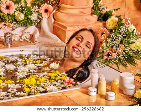 Woman relaxing at flower water spa. Luxury bathroom with flowers. - stock photo