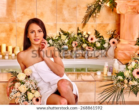 Woman relaxing at flower water spa. White towel. - stock photo