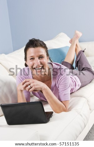 Woman relaxing at home on sofa with laptop surfing the internet - stock photo