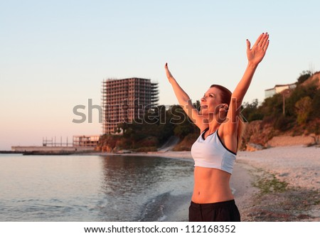 Woman relaxing at the beach with arms open enjoying her freedom - stock photo