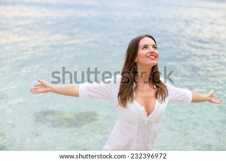 Woman relaxing at the beach with arms open enjoying her freedom,  independence, good health, time off. - stock photo