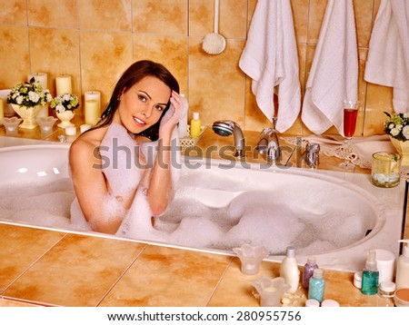 Woman relaxing at water in bubble bath on towels background. - stock photo