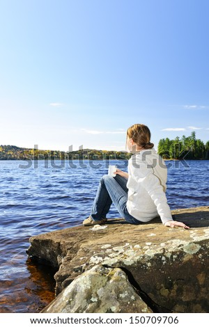 Woman relaxing by beautiful lake on sunny fall day in Algonquin Park, Canada - stock photo
