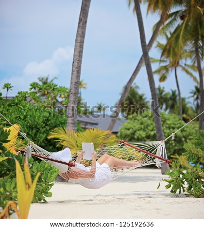 Woman relaxing in a hammock and reading a book on a beach in Maldives, shot with a tilt and shift lens - stock photo