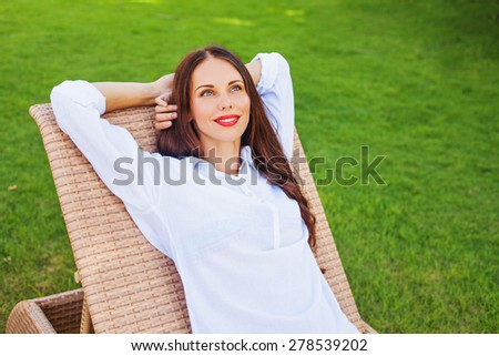 woman relaxing in a lounger over green grass - stock photo