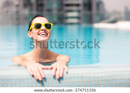 Woman relaxing in a luxurious pool. - stock photo