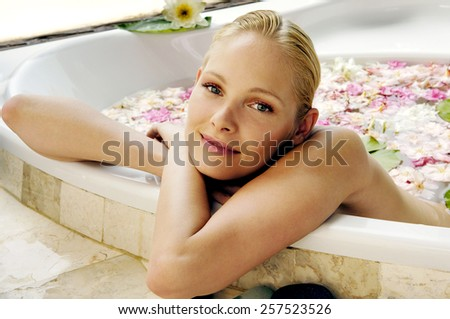 woman relaxing in bath with petal. - stock photo
