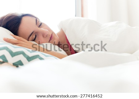 Woman relaxing in bed during the morning
