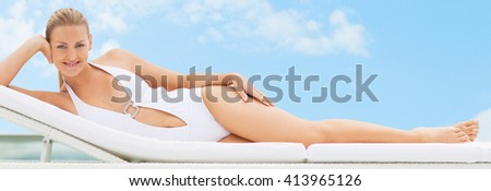 Woman relaxing in deck chair near  pool