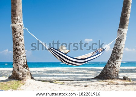 Woman relaxing in hammock at the beach - stock photo