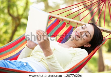 Woman Relaxing In Hammock With  E-Book - stock photo