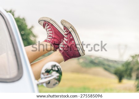 Woman relaxing in her car while driving in the countryside - Young  cool girl with shoes out of the automobile window to enjoy the view - stock photo