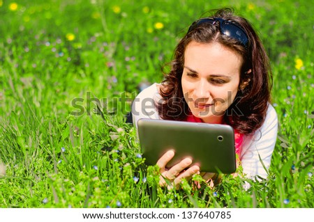 Woman relaxing in nature and using a digital tablet