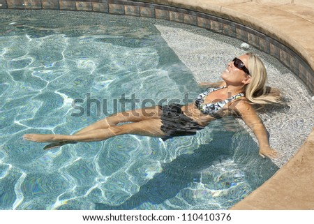 Woman relaxing in pool - stock photo