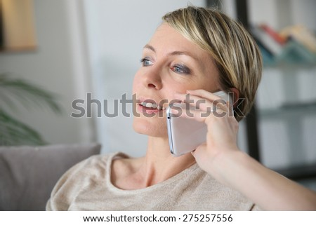 Woman relaxing in sofa talking on mobilephone - stock photo