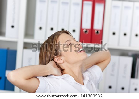 Woman relaxing in the office sitting back in her chair with her eyes closed and hands behind her neck - stock photo
