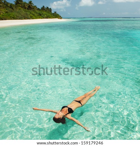 Woman relaxing  in the sea - stock photo