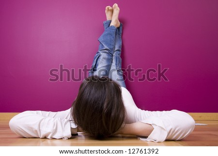 woman relaxing, looking a t her new painted wall (focus on the head) - stock photo