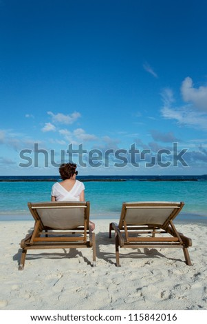 Woman relaxing on a beach chair looking at the Ocean.