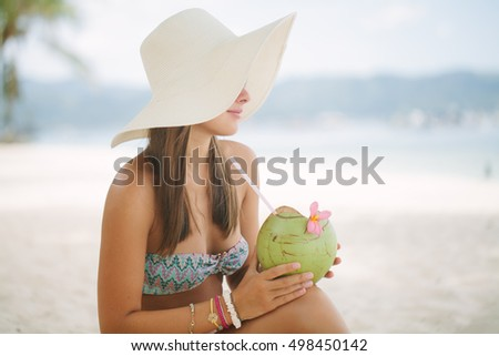 Woman relaxing on a paradise beach with coconut