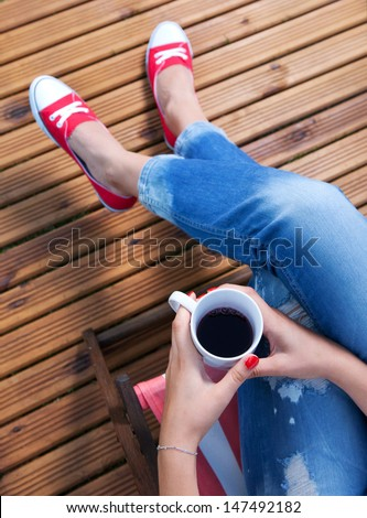 Woman relaxing on a patio - stock photo