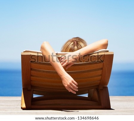 woman relaxing on deck chair - stock photo