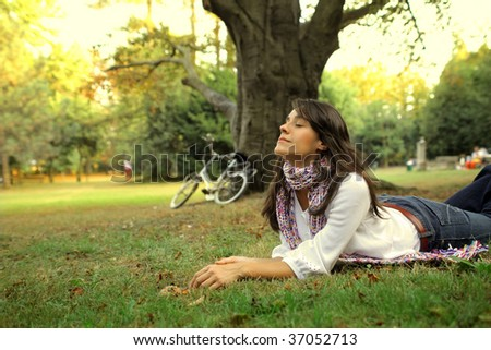 woman relaxing on grass field after a bike ride - stock photo