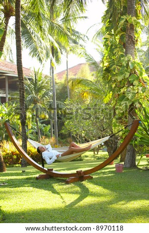 Woman relaxing on hammock at exotic surrounding at bali indonesia