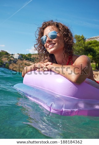 Woman relaxing on inflatable mattress.