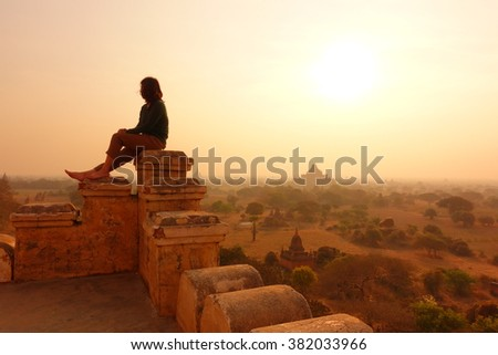 Woman Relaxing on Old Pagoda in Bagan, Myanmar at Silhouette Sunrise - stock photo