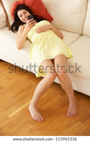 Woman Relaxing On Sofa Sending Text Message - stock photo