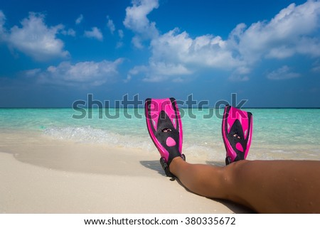 Woman relaxing on summer beach vacation holidays lying in sand. Flippers in legs. Diver fins - stock photo