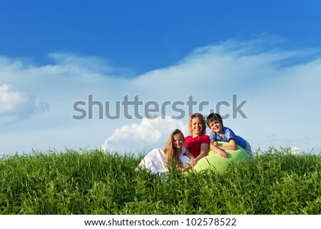Woman relaxing outdoors with her kids - sitting in the grass - stock photo