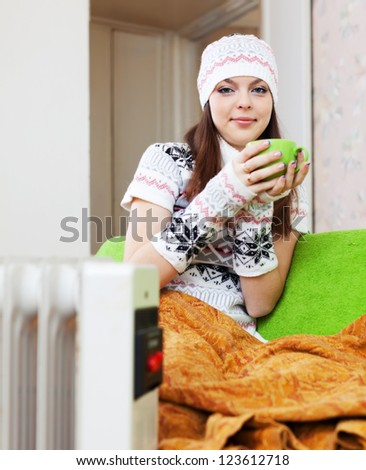 woman relaxing with cup near heater at home in winter