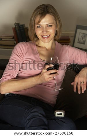 Woman Relaxing With Glass Of Wine Watching Television