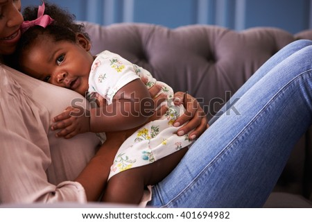 Woman relaxing with her toddler daughter, mid-section crop - stock photo