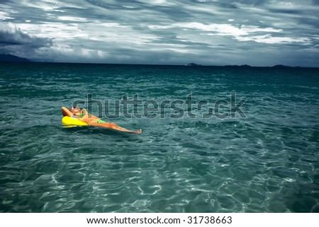 Woman relaxing with yellow tube in bad weather - stock photo