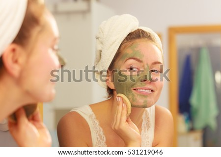 Woman removing facial dried clay mud mask with sponge in bathroom in front of mirror. Skin care. Girl taking care of her complexion. Beauty spa treatment.