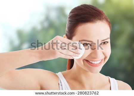 Woman removing make up with cotton pad. - stock photo
