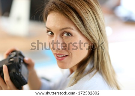 Woman reporter in office looking at photo camera - stock photo