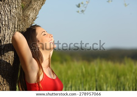 Woman resting and relaxed comfortable leaning in a tree in a meadow in summertime - stock photo