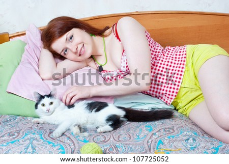 Woman resting on a bed with a kitten - stock photo