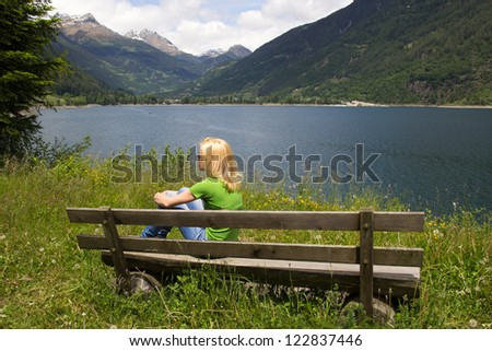 Woman resting on a bench near the lake Poschiavo in the Swiss Alps - stock photo