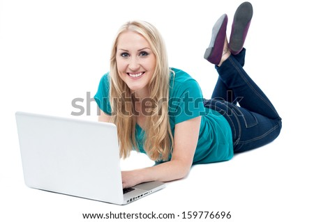 Woman resting on studio floor and operating laptop - stock photo